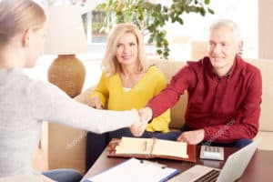 Couple shaking hands with broker
